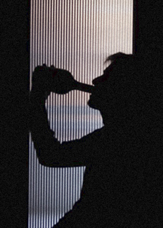 Man in silhouette behind frosted glass door drinking from spirits bottle